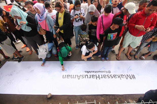 Sekelompok warga menandatangi spanduk #MakassarHarusAman