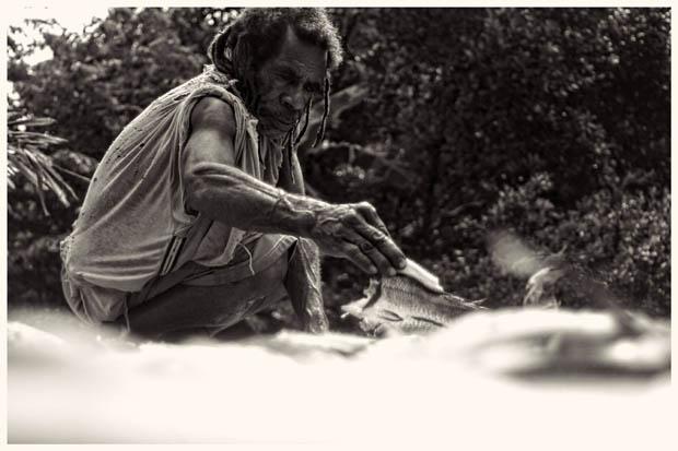Seorang warga sedang menjemur ikan gator. Selain ikan gator, mereka juga beternak buaya. Dagingnya untuk dimakan, kulitnya dijemur dan dijual kepada pengepul.