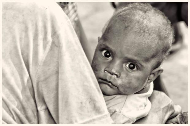 Tatapan tajam seorang anak Rawa Biru dalam gendongan ibunya. Di kampung ini saya menemukan beberapa anak albino, berkulit lebih terang dan berambut keriting pirang.