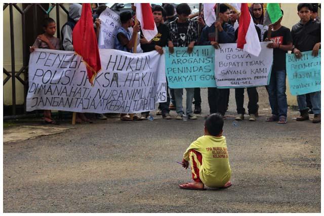 Seorang anak kecil mencangkung di depan para demonstran yang menuntut agar Fadli Rahim dibebaskan dari segala tuduhan.